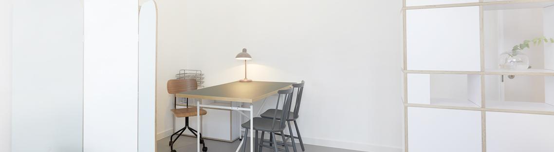 Zimmerecke mit Tisch und Stühlen und einer Schreibtischlampe