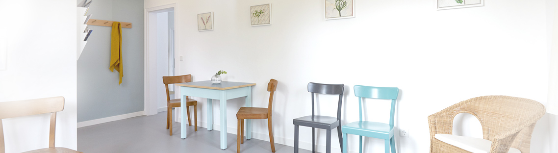 Wartezimmer mit Holzstühlen, kleiner Tisch, ein Korbstuhl
